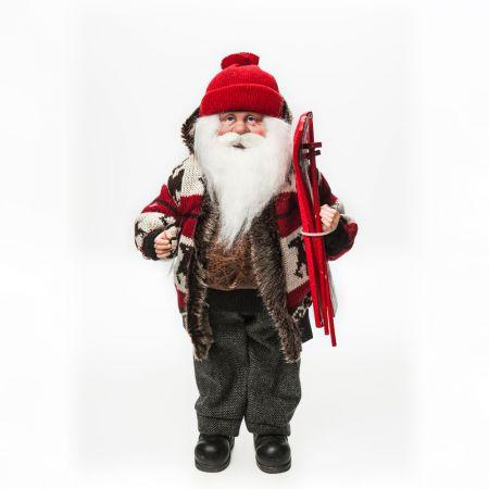 Διακοσμητικός Άγιος Βασίλης που κρατάει σκι με παλτό και πλεκτό σκούφο.